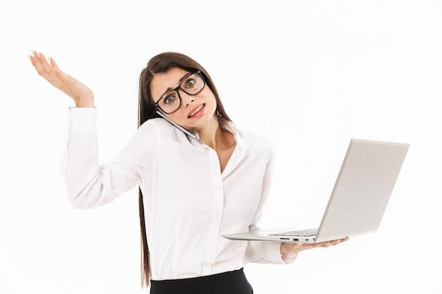 Aantrekkelijke drukke jonge zakenvrouw die geïsoleerd over een witte muur staat, een laptop vasthoudt en op een mobiele telefoon praat