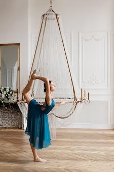 Aantrekkelijke elegante ballerina in de buurt van de kristallen kroonluchter