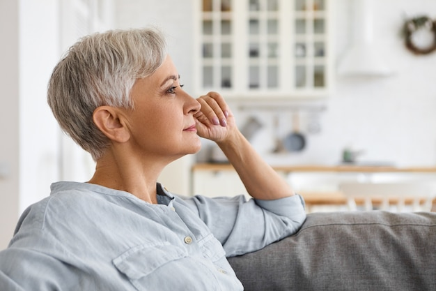Aantrekkelijke elegante grijze haren vrouwelijke gepensioneerde m / v in stijlvol blauw shirt zittend op de bank in de woonkamer, haar gezicht aan te raken, na te denken over haar leven. mensen, lifestyle, interieur en gezelligheid concept