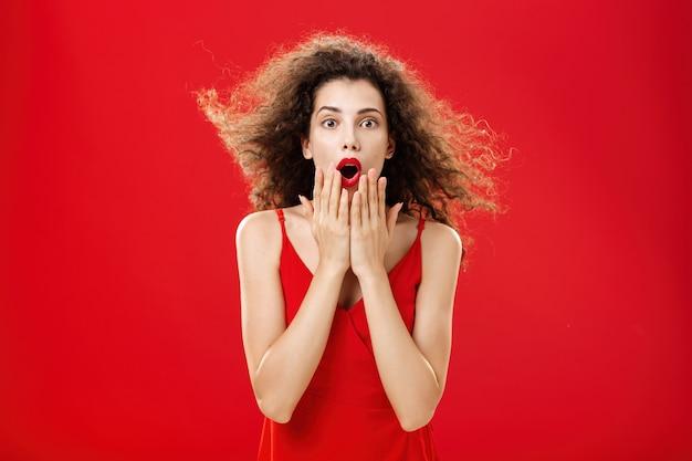 Aantrekkelijke elegante jonge vrouw in rode avondjurk met krullend haar dat op de wind zwaait en zegt wow onder de indruk en opgewonden die geopende mond bedekt van verbazing over rode achtergrond.