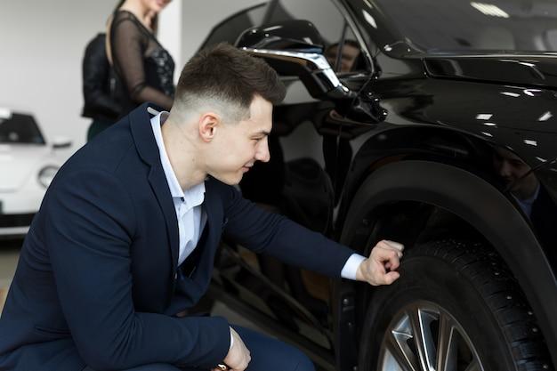 Aantrekkelijke elegante man onderzoekt wielen van een nieuwe auto te koop bij dealer. knappe mannelijke bestuurder die nieuwe te kopen auto kiest
