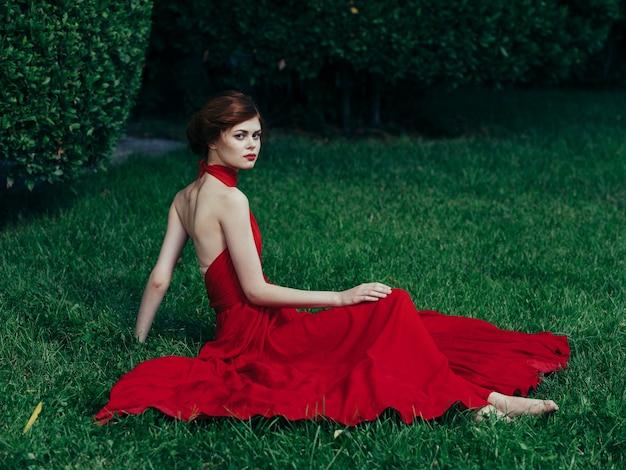 Aantrekkelijke elegante vrouw ligt buiten op de rode jurk van gras