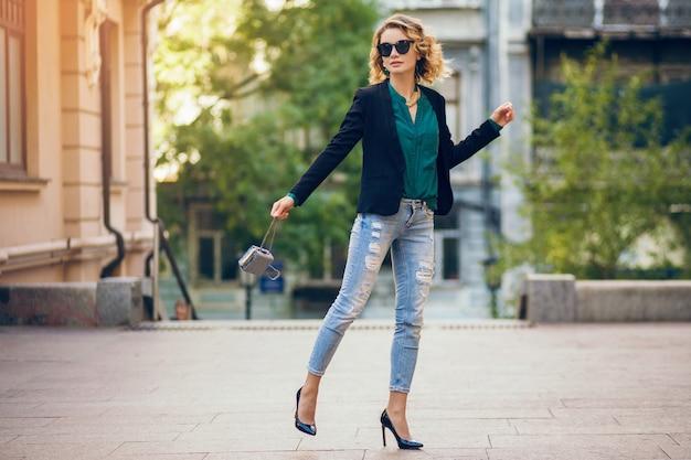 Aantrekkelijke elegante vrouw lopen in de stad straat op schoenen met hoge hakken, wesaring spijkerbroek, zwarte jas, groene blouse, zonnebril, kleine portemonnee, modetrend van de zomer, slanke mooie dame