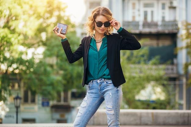 Aantrekkelijke elegante vrouw lopen in stad straat met portemonnee, zwarte jas, zelfverzekerd en sexy dragen,