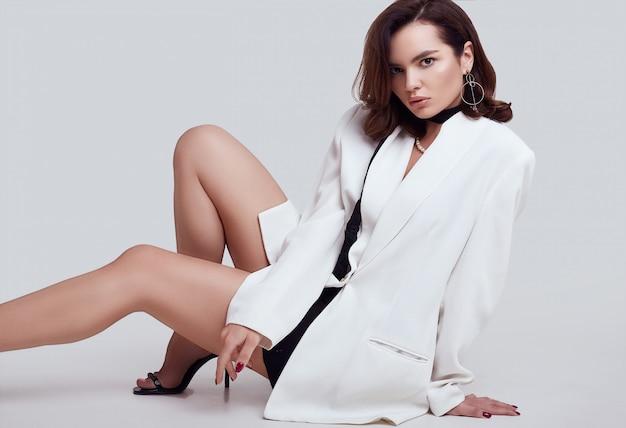 Aantrekkelijke elegante vrouw met donker haar in mode wit pak
