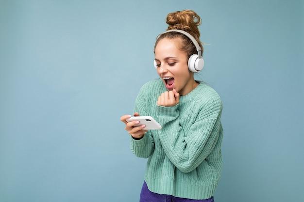 Aantrekkelijke emotionele positieve jonge vrouw die blauwe geïsoleerde sweater draagt