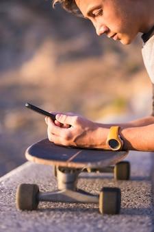 Aantrekkelijke en doordachte tienerjongen ontspannen met een skateboard en zittend op een bankje houden en gebruiken van een smartphone voor netwerken tijdens een zonnige dag, buitenshuis