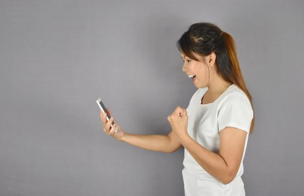 Aantrekkelijke en glimlachende vrouwen in smartphones houden en t-shirts die ja gebaar tonen