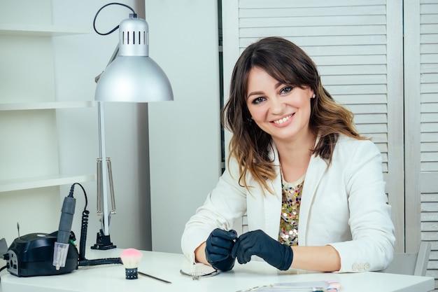 Aantrekkelijke en jonge manicure professionele (master of manicure) vrouw in een witte jas en zwarte rubberen handschoenen zit in een schoonheidssalon. het concept van nagelverzorging en schoonheid