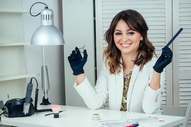Aantrekkelijke en jonge manicure professionele (meester van manicure) vrouw in een witte jas en zwarte rubberen handschoenen houdt een nagelvijl in een schoonheidssalon. het concept van nagelverzorging en schoonheid
