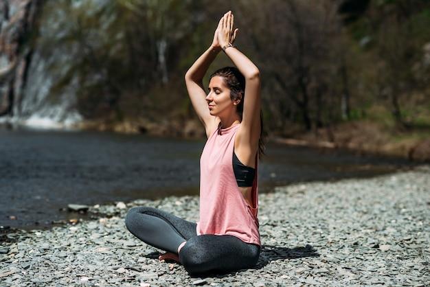 Aantrekkelijke en jonge vrouw die yoga doet bij de rivier bij dageraad, close-up. yoga in de frisse lucht. gelukkige vrouw die yoga-oefeningen doet. meditatie in de natuur. een vrouw die yoga beoefent bij de rivier. ruimte kopiëren