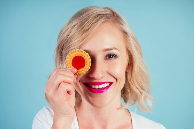 Aantrekkelijke en lachende vrouw blonde met make-up en lippenstift op lippen kleur fuchsia houdt een calorierijk koekjeskoekje in de hand in de studio op een blauwe achtergrond