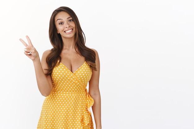 Aantrekkelijke enthousiaste schattige vrouw in gele zomerjurk, verkleeddatum, vredes- of overwinningsteken tonen, zacht en vrolijk lachend, geniet van vakantie