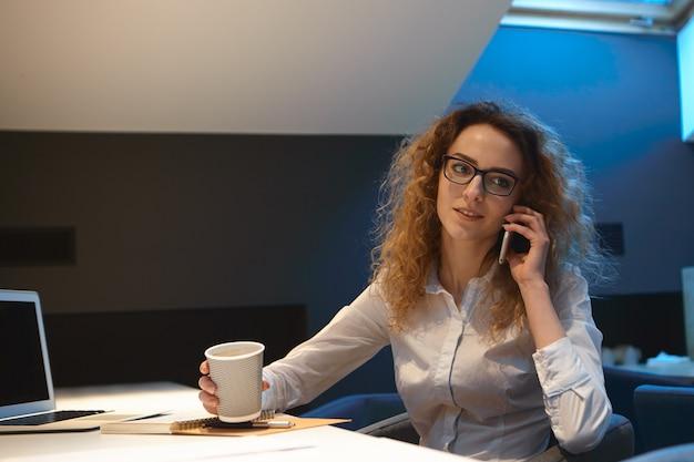 Aantrekkelijke ernstige jonge vrouwelijke ondernemer in formeel overhemd en rechthoekige glazen