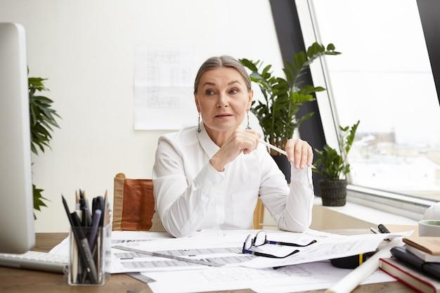 Aantrekkelijke ervaren 50-jarige vrouwelijke hoofdarchitect met grijs haar die tekeningen op bureau voor haar bestudeert, aantekeningen maakt en de datum vergelijkt met metingen op de computer, met een gerichte blik