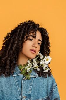 Aantrekkelijke etnische peinzende vrouw met bloemen