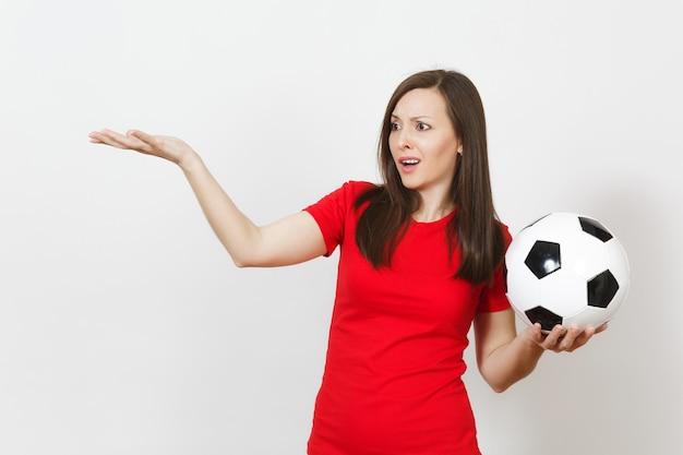 Aantrekkelijke europese jonge verdrietig overstuur vrouw, voetbalfan of speler in rood uniform houdt voetbal, maakt zich zorgen over het verliezen van team geïsoleerd op een witte achtergrond. sport, voetbal, lifestyle concept.