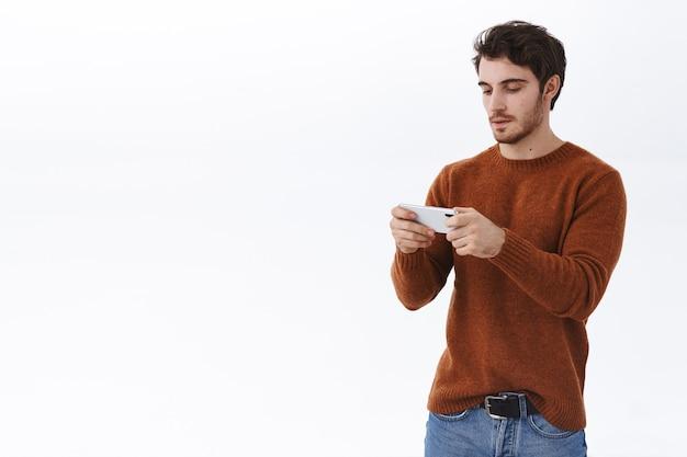 Aantrekkelijke europese man die mobiele telefoon gebruikt, smartphone horizontaal houdt en kijk naar het scherm gericht op het passeren van het niveau
