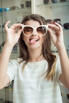 Aantrekkelijke europese student die gezichten maakt terwijl bij het winkelen met vriendin