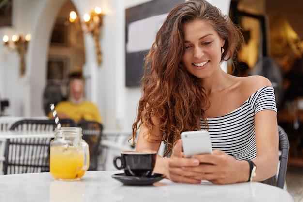 Aantrekkelijke europese vrouw met gelukkige uitdrukking gebruikt moderne mobiele telefoon in gezellige koffieshop