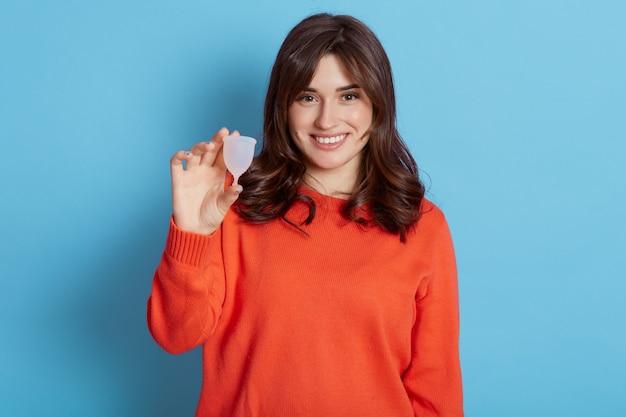 Aantrekkelijke europese vrouw met menstruatiecup en glimlachen, staande tegen blauw