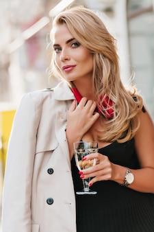 Aantrekkelijke europese vrouw met wijnglas draagt beige jas zachtjes glimlachend. spectaculaire blonde dame in zwarte jurk en zilveren polshorloge poseren met plezier op evenement.