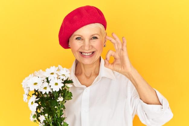 Aantrekkelijke europese vrouwelijke gepensioneerde m / v met blauwe ogen poseren geïsoleerd in rode hoofddeksels vreugde uiten, witte madeliefjes vasthouden en ok gebaar tonen als teken van goedkeuring, breed glimlachend op camera