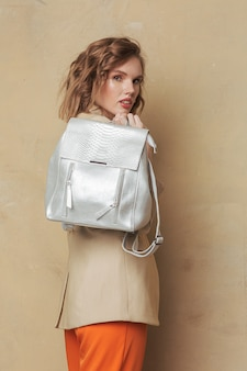 Aantrekkelijke fashionista poseren met een zilveren tas in slimme vrijetijdskleding.