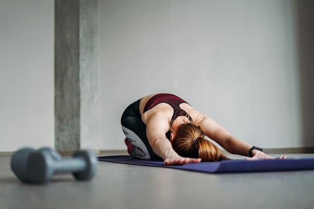 Aantrekkelijke fit jonge vrouw in sportkleding meisje traint met halters die zich uitstrekt in de loft studio