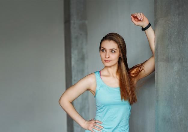 Aantrekkelijke fit lachende jonge vrouw sport slijtage fitness meisje model portret bij de thuis loft studio training klasse