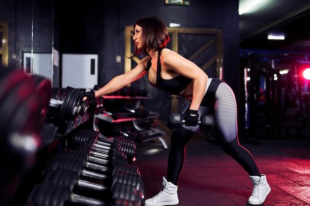 Aantrekkelijke fit middelbare leeftijd vrouw in de sportschool hurkt met een barbell. vrouw training terug