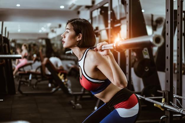 Aantrekkelijke fit vrouw training met barbell in gym fitness