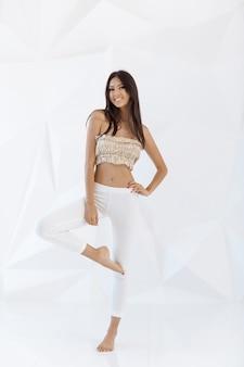 Aantrekkelijke fitness aziatische vrouw binnenshuis op witte abstracte veelhoek achtergrond. casual gemengd ras