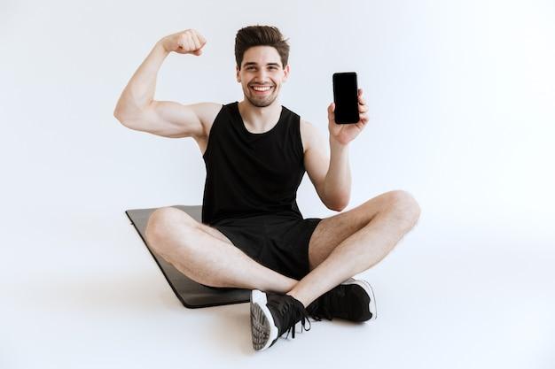 Aantrekkelijke fitte jonge sportman zittend op een fitnessmat met geïsoleerde mobiele telefoon, spieren buigend terwijl hij een lege mobiele telefoon toont