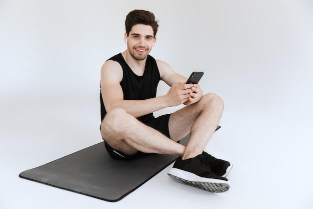 Aantrekkelijke fitte jonge sportman zittend op een fitnessmat met mobiele telefoon, luisterend naar muziek met draadloze oortelefoons geïsoleerd