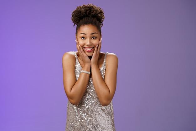 Aantrekkelijke geamuseerde charmante gefascineerde afro-amerikaanse vrouw in stijlvolle zilveren jurk pers handen wangen verbaasd dankbaar ontvangen indrukwekkend spannend geschenk glimlachend opgetogen, blauwe achtergrond.