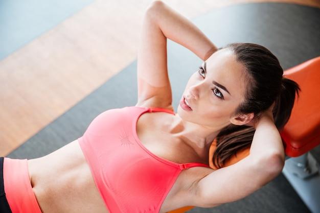 Aantrekkelijke geconcentreerde jonge vrouwenatleet die oefeningen doet die op bank in gymnastiek liggen