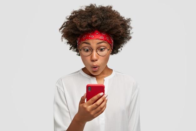 Aantrekkelijke gekrulde donkere huid vrouw met afro kapsel kijkt opgewonden op het scherm van de slimme telefoon, onder de indruk van de berichtinhoud van een vriend, heeft gezichtsuitdrukking verrast, staat binnen