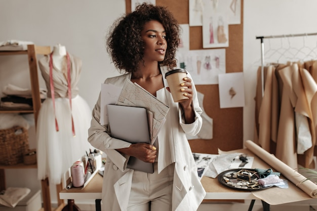 Aantrekkelijke gekrulde donkere vrouw in witte jas, broek en top leunt op bureau in kantoor van modeontwerper