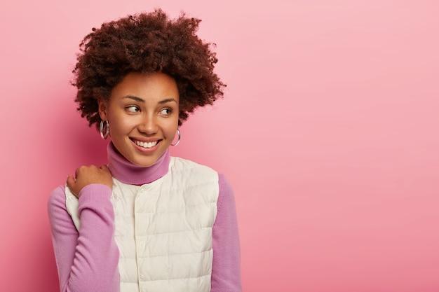 Aantrekkelijke gekrulde haired vrouw raakt schouder, draagt coltrui en wit vest, in goed humeur