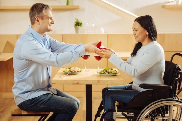 Aantrekkelijke gelukkig blonde man glimlachend en stelt voor aan zijn mooie geliefde donkerharige gehandicapte vrouw en houdt een ring vast tijdens een romantisch diner