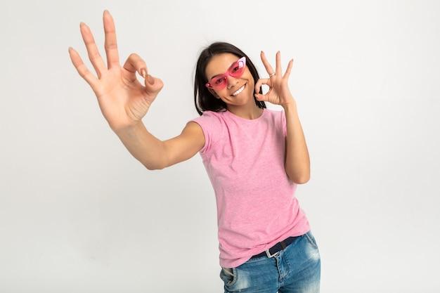 Aantrekkelijke gelukkig grappige emotionele vrouw in roze t-shirt geïsoleerde armen naar voren ok teken tonen