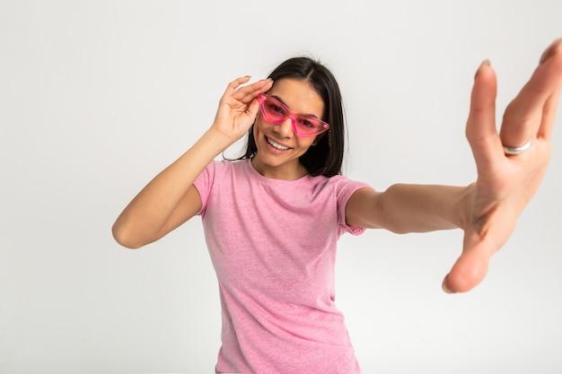 Aantrekkelijke gelukkig grappige emotionele vrouw in roze t-shirt geïsoleerde armen naar voren