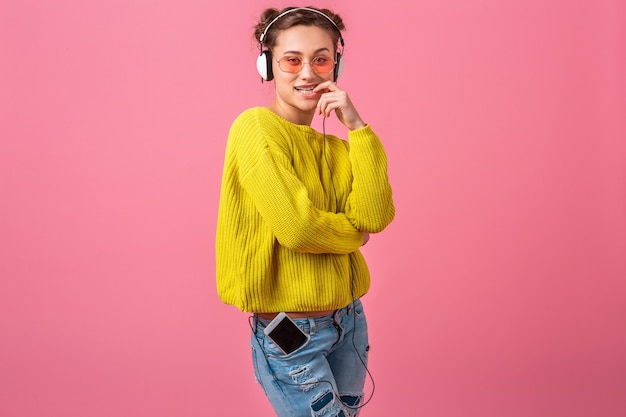 Aantrekkelijke gelukkig grappige flirterige vrouw luisteren naar muziek in koptelefoon gekleed in hipster kleurrijke stijl outfit geïsoleerd op roze muur, gele trui en zonnebril dragen, plezier