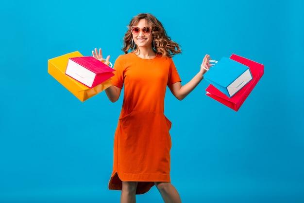 Aantrekkelijke gelukkig lachend stijlvolle vrouw shopaholic in oranje trendy oversized jurk springen met boodschappentassen bedrijf op blauwe achtergrond geïsoleerd
