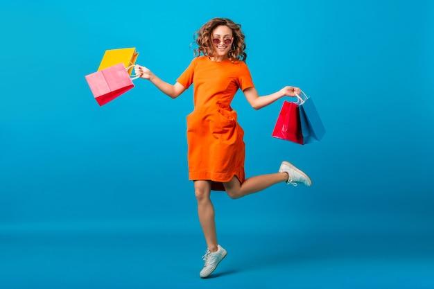Aantrekkelijke gelukkig lachend stijlvolle vrouw shopaholic in oranje trendy oversized jurk springen met boodschappentassen op blauwe studio achtergrond geïsoleerd
