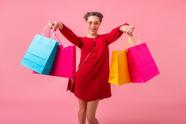 Aantrekkelijke gelukkig lachend stijlvolle vrouw shopaholic in rode trendy jurk springen uitgevoerd bedrijf kleurrijke boodschappentassen op roze muur geïsoleerd, verkoop opgewonden, lente zomer modetrend