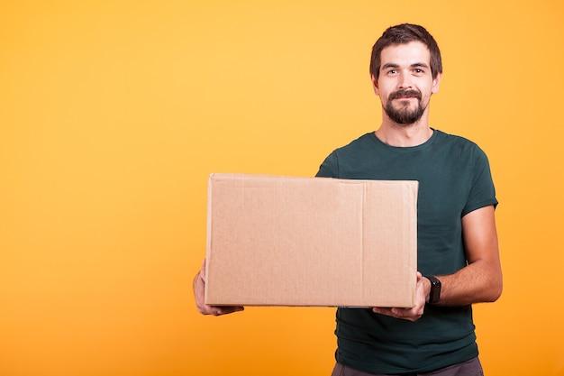Aantrekkelijke gelukkig lachende bezorger met een kartonnen doos in zijn handen op gele achtergrond in studio