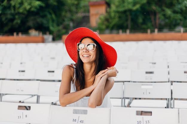 Aantrekkelijke gelukkig lachende vrouw gekleed in witte jurk, rode hoed, zonnebril zittend in zomer openluchttheater op stoel alleen, lente streetstyle modetrend