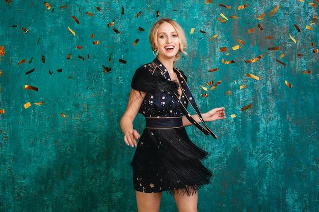 Aantrekkelijke gelukkig lachende vrouw in stijlvolle zwarte jurk